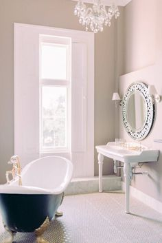 bathroom goals with Victorian free standing bath tub in navy blue with gold feet and furnishings, large French antique style mirror and ceramic porcelain sink with crystal chandelier. floor to ceiling windows, neutral painted walls with a muted palette