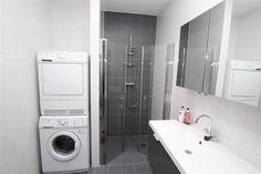 Kleine badkamer met plaats voor de wasmachine en droger.