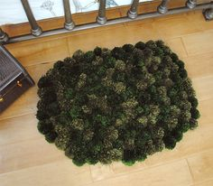 DIY Pom Pom Rug  4: I love the color combination- reminds me of moss...  This would look great done in various shades if cream (and boy, I have a lot of scrap yarn in those tones ; P ) to get a sheep skin look, I think.