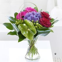 A stylish tropical anthurium takes centre stage in this vase, arranged together with roses, gerberas and luxury foliages makes a stunning impression. Other flowers will vary depending upon seasonal availability See more at: http://www.nottinghamflorist.com/shop/local/flowers/contemporary.shtml