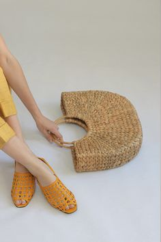 I want every piece in this image in my life now! Straw circle tote. Mustard woven slides. Lemon linen pants.