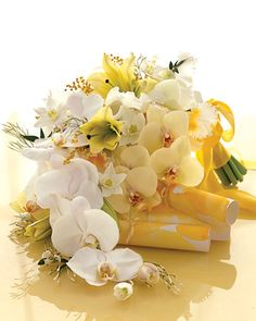 This waterfall of Conca d'Or lilies, eucharis lilies, jasmine, snow berries, phalaenopsis orchids, and cattleya orchids spilling forth from a band of yellow silk ribbon is as graceful as it is exuberant.