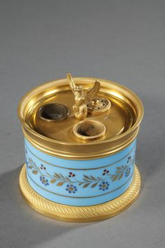 A small circular inkwell in turquoise opaline decorated with a gold, red and dark blue  flowery crown flanked with golden stripes. This decoration is characteristic of Jean Baptiste Desvigne