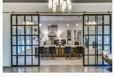 Suspended barn doors with clear glass and black frames. Designers handles and NO bottom track to separate the kitchen and the dining room. Made by The Sliding Door Company.