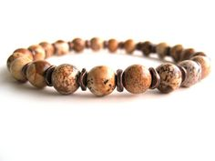 Masculine men's beaded stretch bracelet featuring 8mm picture jasper beads and antiqued copper accent beads. The picture jasper beads have amazing patterns with brown, black, tan and rust hues throughout. This is a rugged and manly bracelet that any man would love! Wear as shown or stacked with your favorite watch or more bracelets for a stylish option.