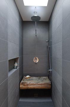 Dunkle Dusche mit Feinstein verkleidet. Sitzbank aus Altholz. Chromoberflächen sowie eine Wandnische.