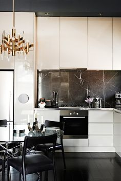 Amazing space. Cream high gloss cabinets, black ceiling, black granite slab as backsplash, stainless steel counter, chandelier. So sophisticated and masculine.