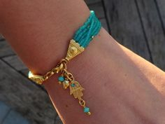 Sheer turquoise-green color multilayer seed beaded bracelet with gold plated hamsa charm.