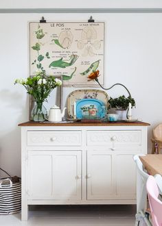 Dining area with vintage sideboard and vintage finds, including French botanical poster.
