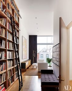 Floor-to-ceiling oak bookshelves distinguish the library of a New York City townhouse renovated by architect Annabelle Selldorf.