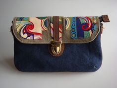 Esta bolsa possui divisória e alça removível. Pode se transformar em carteira, bolsa de ombro ou transversal. Ela é feita de lona estonada e detalhe da tampa em tecido de algodão. R$95,00