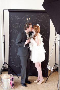 Create a fun and whimsical doodle photo booth background for your wedding photos with a black seamless paper backdrop and gold marker.