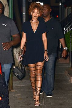 Rihanna channels the '90s wearing a sleek choker, LBD and lace up gladiators. Shop her outfit here: