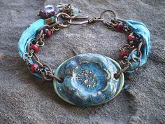 Patinaed Garden Bracelet.  Brass bracelet with a turquoise ceramic focal and sari silk on Etsy by TheJunquerie.