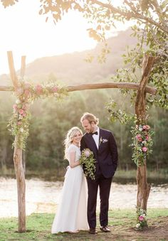 (CEREMONY) Your rustic twig arch with flowers placed around one top corner like shown in picture. And then a half circle of flowers petals where they will stand in front of arch.