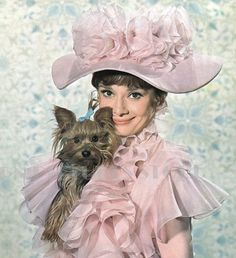 """The actress Audrey Hepburn photographed with Assam of Assam (her Yorkshire Terrier) by Bob Willoughby at the Warner Brothers Burbank Studios, located on Warner Boulevard, in Burbank, a city in Los Angeles County, in Southern California (USA), during a photo shoot for the publicity material of her new movie """"My Fair Lady"""", in September 1963. Audrey was wearing:Costume by Cecil Beaton (an afternoon gown, accompanied by a ruffled shawl), created specially for the wardrobe of her character…"""