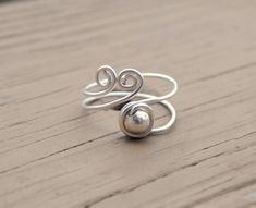 Like ocean waves, spirals just entice me. I love this look of spiral jewelry and when I added this little silver bead, it just topped off this new ring. It is wrapped with 18 gauge non tarnish wire. Although it is slightly adjustable, I need to have a ring size for the perfect fit.