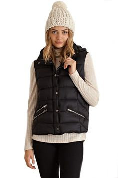 Solid padded zipper puffer vest featuring buttons on front. Zippered pockets on sides. Non-sheer. Unlined. Woven. Lightweight. 100% NYLON. Imported.