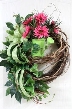 Sitting on the garland is a lime green watering can with pink daisies with lime green centers! Also added, is a beautiful country lime green checked bow that flows through out the wreath, along with leaves and ivy with dark pink stems. This wreath will surely brighten your front door for spring and summer. Florals From Home