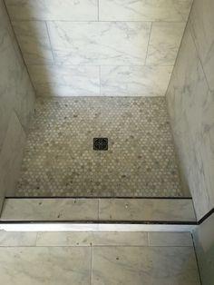 "12x24 Carrara look tile shower with 1"" Carrara hex shower floor and bronze schluter strip. Superior Development, Llc. Nashville builder. Design by Jessica Powers."
