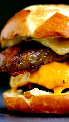 Sweet and Smoky Bacon Brat Burger Recipe ~ A quarter pound beef burger is topped with cheese, brown sugar glazed bacon and a split bratwurst.  This glorious mountain of meat is then sandwiched between two halves of a pretzel bun slathered with smoky mustard.  Forget the sides!  This burger is a complete meal!