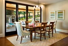 The chairs at the head of the table are in a light blue, while the rest of the dining set is a rich hardwood. French doors behind the table lead out onto the covered patio with a fire place.