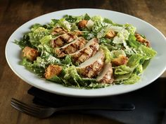 CAESAR SALAD Romaine lettuce tossed in our homemade Caesar dressing, topped with garlic croutons and shaved Parmesan cheese. Add grilled chicken,* grilled shrimp* or grilled salmon* for a little extra.