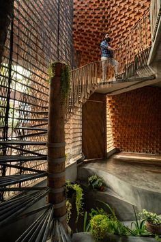 A metal staircase leads along the side of the reclaimed screen. India Architecture, Architecture Office, Brick Architecture, Sustainable Architecture, Compound Wall, Construction Firm, Curved Walls, Architectural Features, Architectural Digest