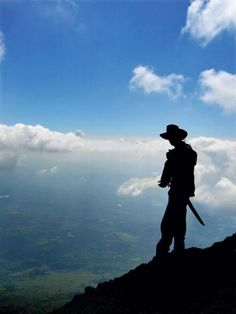 Silhouette of a man with a machete, half way up the active Volcano Pacaya in Guatemala.