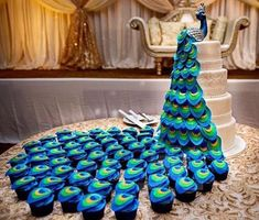 a wedding backdrop with a sugar peacock on top and matching cupcakes that form i. a wedding backdrop with a sugar peacock on top and matching cupcakes that form its tail. Peacock Cake, Peacock Wedding Cake, Peacock Decor, Peacock Cupcakes, Wedding Flowers, Peacock Wedding Decorations, Peacock Wedding Colors, Peacock Shoes, Peacock Feathers