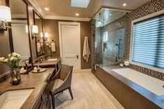 A double vanity with a seating area creates a hotel-like atmosphere in this spacious bathroom. A modern bathtub and glass-encased shower keep things feeling fresh, while large framed mirrors above the vanity enhance the spacious quality of the room.