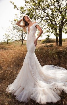 GALA-702 Embroidered chantilly lace mermaid dress with off-the-shoulder detail plunging into a deep V at front. The dress has a multi-layered skirt made of silk tulle, in various shades and lace. The back is very low and supported by illusion tulle.
