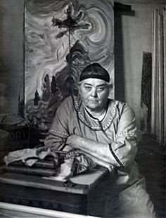 "Emily Carr in her studio with her painting, ""Sunshine and Tumult,"" behind her, c. 1936."