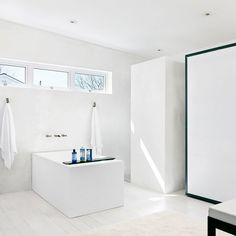 This ultra-minimal residence is light filled and plastered in a subtle stucco effect, giving the room a hint of texture. The simple rectangular bath is perpendicular to the wall and centered in...
