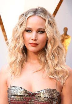 2018 Oscars - Jennifer Lawrence  Jennifer Lawrence rocking her natural curls, a burnt orange lipstick, and metallic cat-eye on the Oscars red carpet.