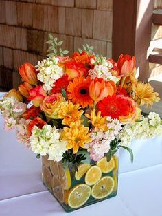 Orange slices set the tone for this cheerful arrangement of roses, gerbera daisies, stock, chrysanthemums, and tulips.