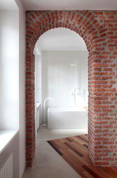 Pared y arco de ladrillo de campo visto, contrastado con el resto de paredes lisas y blancas.
