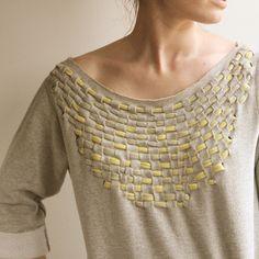 Una idea sencilla que queda muy linda es agujerear la tela y pasar el trapillo para hacer un detalle en las prendas como vemos en esta camiseta gris con ...