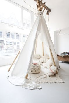 A Teepee Made from Branches and White Muslin