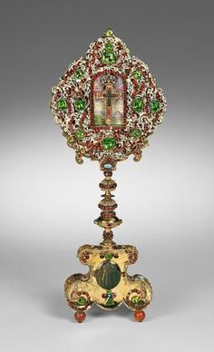 MONSTRANCE 1668: Preserved in the niche of the monstrance, in front of a painted miniature of Jerusalem, is a particle of the Cross. The cruciform relic is enclosed in a receptacle of rock crystal and gold, und bears a diamond crown. Around the niche is a wider border of enamelled scrollwork, bands of garnets and large chrysolites. The tall stand, resembling a candlestick in form, is decorated in similar, albeit less ornate fashion.
