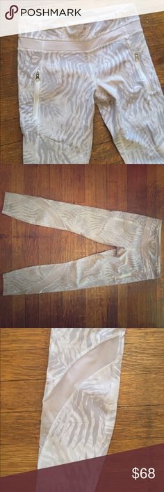 Never worn Lulu grey feathered pattern leggings! Grey feathered pattern leggings, size 6, mesh on the calf (super cute), drawstring in the waistline as well as built in key/card holder for runners convenience! White/grey lululemon athletica Pants Leggings