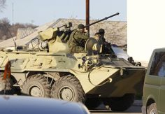 Russian troops forced their way into a Ukrainian airbase in Crimeawith armored vehicles, automatic fire and stun grenades on Saturday, injuring a Ukrainian serviceman and detaining the base's commander for talks.