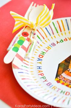 Hole punch the side of a paper plate and attach utensils and napkin with ribbon! Cute idea! Hungry Little Caterpillar 3rd Birthday Party via Kara's Party Ideas | Kara Allen KarasPartyIdeas.com #caterpillarparty #theveryhungrycaterpillar