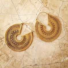These brass earrings are modeled on an antique Rajasthani design which honours the hindu sun god Surya. The filigree and dot work is inspired by