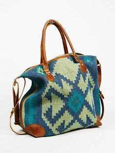 Savoy Weekender | The perfect weekender, made for fabulous getaways or local stays. Colorful woven jute body with leather accents. Zip top closure. Inside features one zip pocket and cotton lining. Top handles and one long adjustable strap for easy carrying.