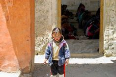 A little girl standing guard outside a community center as the lady folk of the village conduct prayers Small Caps, Girl Standing, Royalty Free Photos, Dream Big, Little Girls, The Outsiders, Folk, Prayers, Community