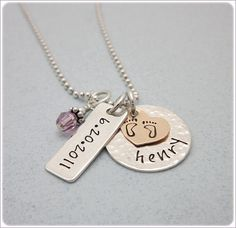 Personalized baby necklace for the new mom featuring two hand stamped charms holding baby's name and birthdate. You can choose to have both of the charms finished textured or smooth or have one of each as pictured in the photo. Layered with a 14kt gold filled heart is stamped with the cutest baby feet. Also includes the corresponding birthstone or freshwater pearl. Comes with your choice of font and sterling silver chain. All hand stamped jewelry arrives wrapped in a sweet gift tin ready for…