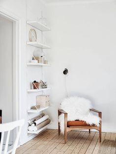 a beautiful corner - white walls, sheepskin and simple shelving