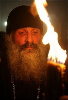 A Christian Orthodox priest holds up a candle lit from the 'Holy Fire' as thousands of Orthodox worshippers gather at Jerusalem's contested Holy Sepulchre Church on 07 April 2007. Thousands of worshippers from five Christian faiths celebrated Easter at the Holy Sepulchre Church -- the traditional site of Jesus's death, burial and resurrection.(AFP/Gali Tibbon)
