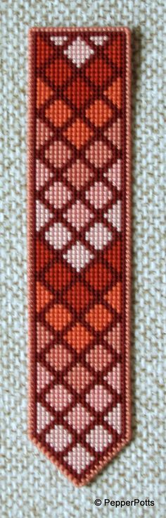 Worked on 14ct plastic canvas in a cross stitch, using various shades of tan and orange stranded cotton leftovers. The diamonds were worked first, then the contrasting lines filled in in a very deep tan stranded cotton. It is backed with thin craft foam using a double sided adhesive film.